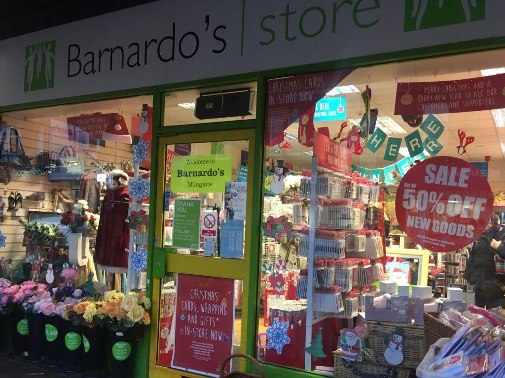 Barnardo's shop displaying 50% off sale and Christmas goods in window.