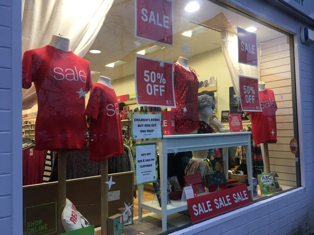 mannequins in Oxfam shop window displaying 50% off sale.