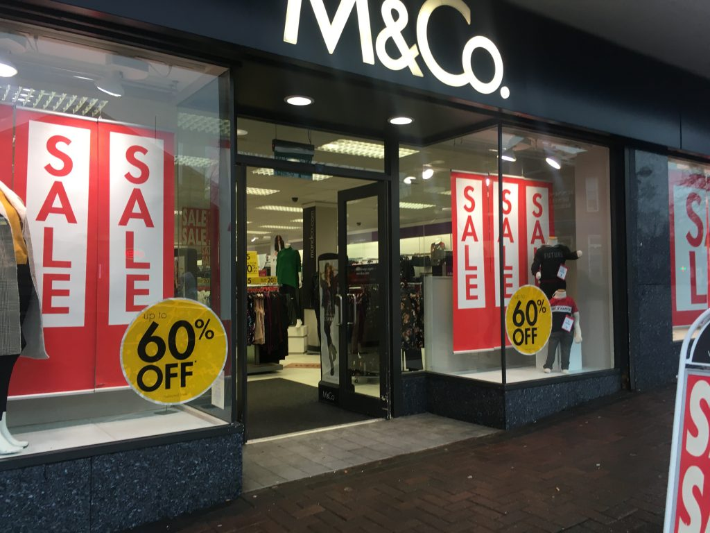 M&Co displaying sales with mannequins in window