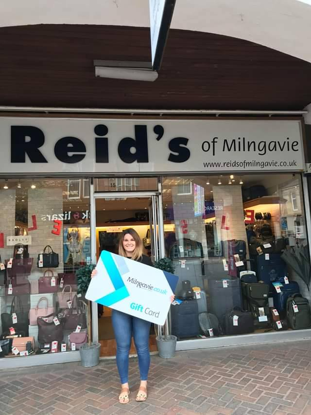 Staff member from Reid's of Milngavie is holding the Milngavie gift card in front of Reid's shop.
